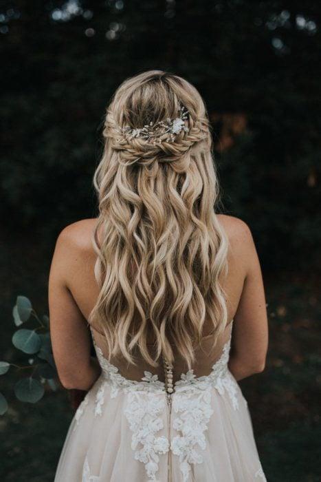 Novia de cabello ondulado con semirecogido en trenza de espiga