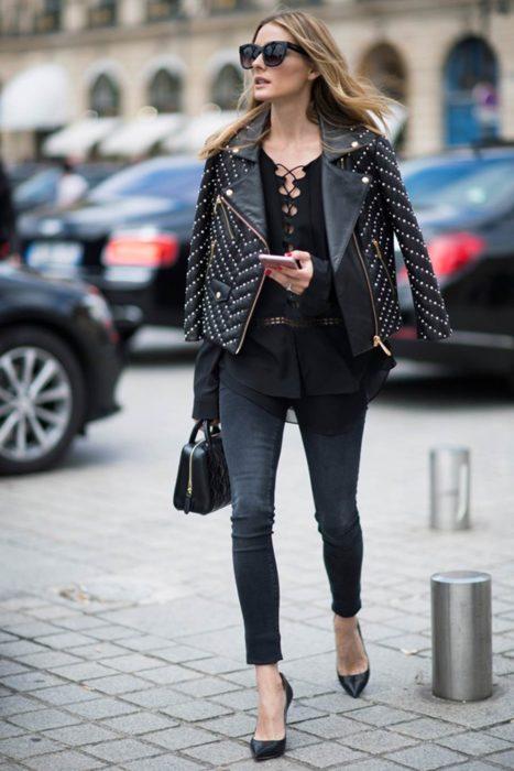 Olivia palermo caminando por las calles mientras mira su celular