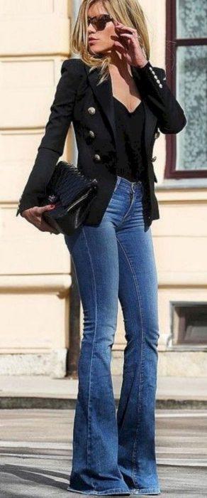 Chica usando unos jeans acampanados, camisa negra y blazer mientras camina por la calle