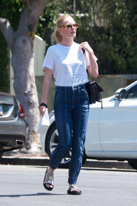 Chica caminando por la calle mientras usa unos jeans, camisa blanca y sandalias