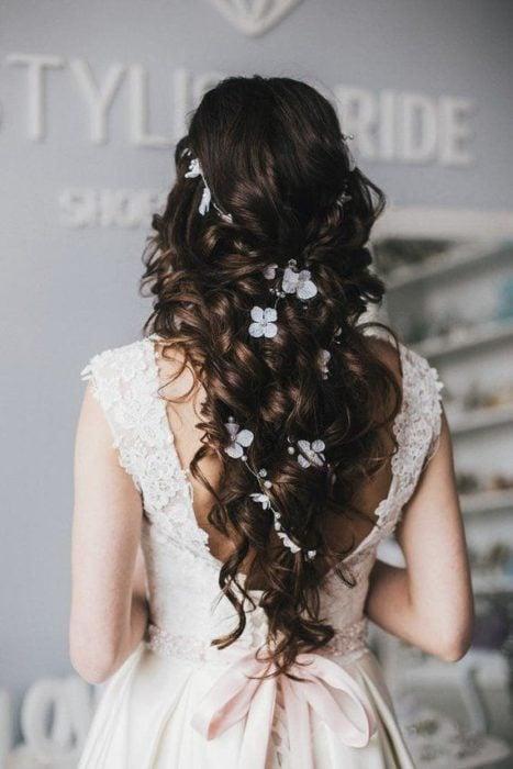 Semirecogido de novia en cabelo rizado tipo twist con adornos florales