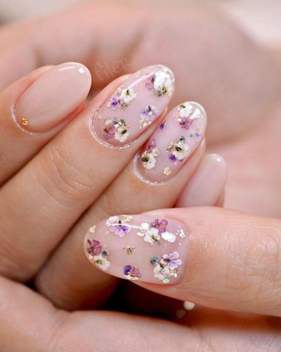 Mujer con manicura de flores lilas en miniatura