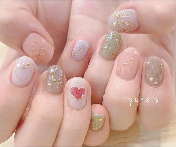 Manicura en tono rosa, gris y verde olivo con deocraco de flores dorados y un corazón