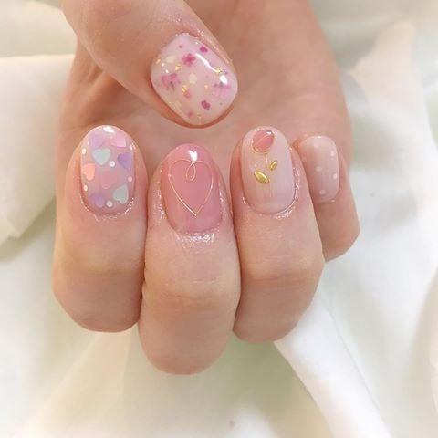 Manicura en tono rosa pastel con pequeñas flores rosas y doradas