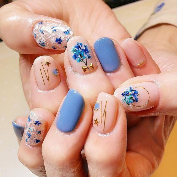 Manicura en tono azul cielo con flores doradas
