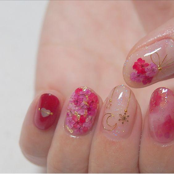 Manicura en tono rosa fucsia con flores doradas miniatura
