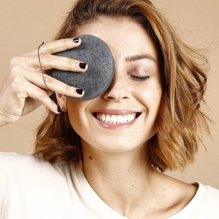 Chica sonriendo con esponja Konjac en uno de sus ojos