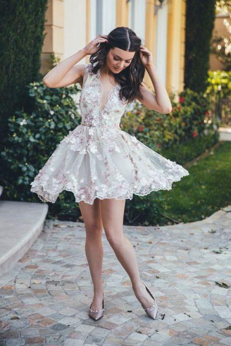 Vestido blanco corto, con escote en V y ensables de flores en toda la tela