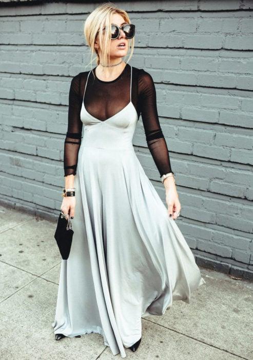 Looks con vestidos y blusas básicas; mujer rubia con peinado casual, lentes de sol grandes, blusa negra transparente, vestido de fiesta gris satinado