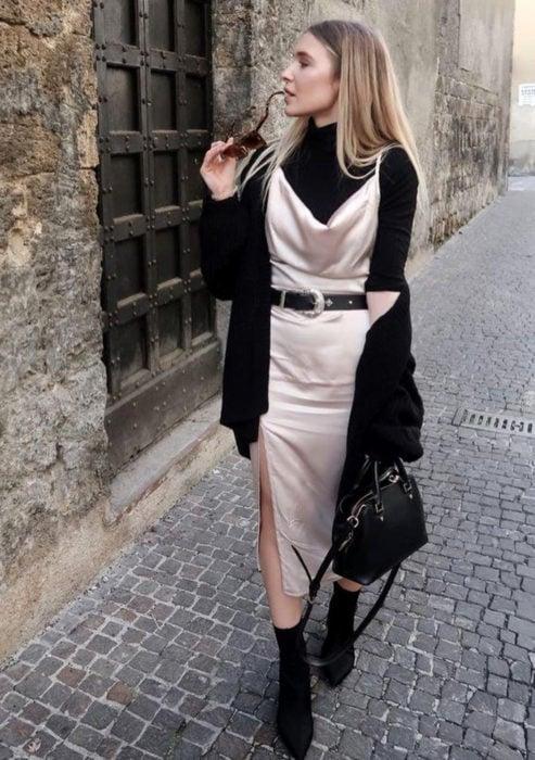 Looks con vestidos y blusas básicas; mujer rubia caminando en calle empedrada, con vestido de satín beige,blusa negra de manga larga y cuello de tortuga, votines