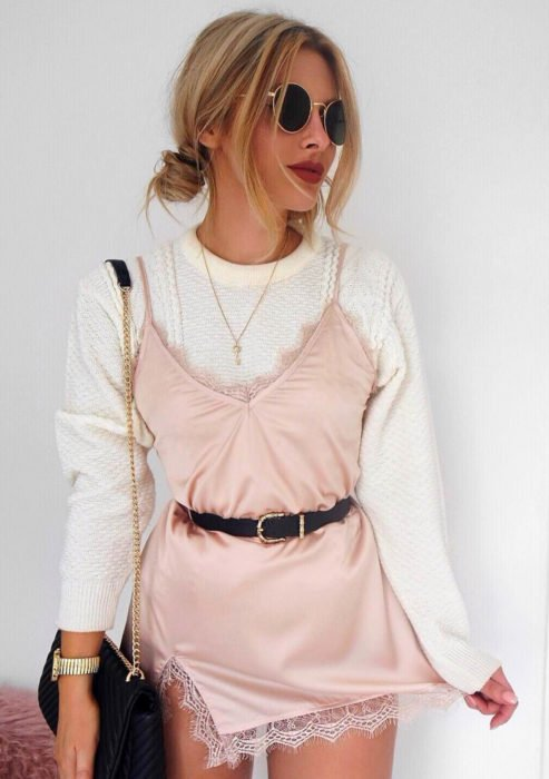 Looks con vestidos y blusas básicas; mujer rubia con peinado de chongos, vestido rosa con suéter tejido blanco