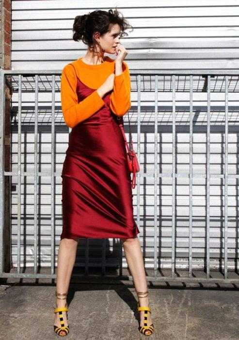 Looks con vestidos y blusas básicas; mujer con vestido satinado rojo, suéter anaranjado y tacones amarillos