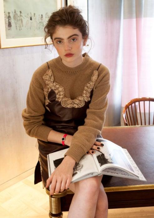 Looks con vestidos y blusas básicas; mujer de cejas pobladas, peinado despeinado, vestido de cuero con encaje, suéter café, sentada en la mesa