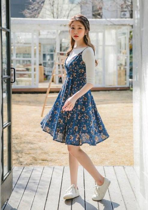 Looks con vestidos y blusas básicas; mujer coreana con peinado de media cola con trenzas, vestido azul de flores con blusa blanca de manga corta y tenis