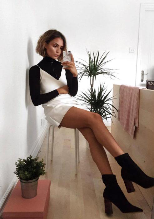 Looks con vestidos y blusas básicas; mujer sentada tomándose selfie frente a espejo, con cabello corto, vestido blanco marfil, blusa negra de manga larga y cuello de tortuga, botines de tacón cuadrado