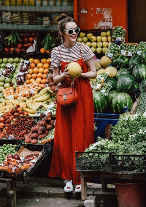 Looks con vestidos y blusas básicas; mujer en frutería en medio de frutas, con peinado de chongo alto, lentes de sol blancos, maxivestido rojo, blusa rayada, tenis