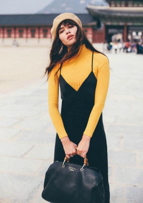 Looks con vestidos y blusas básicas; mujer con vestido negro, blusa amarilla de manga larga, boina francesa