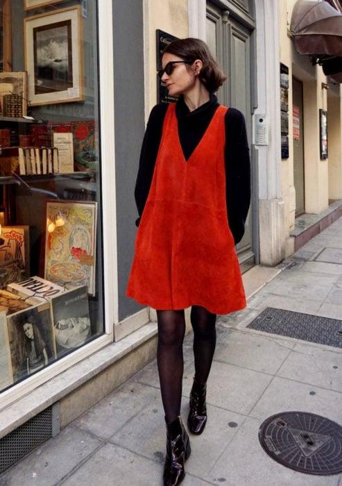 Looks con vestidos y blusas básicas; mujer en la calle viendo escaparates de tiendas, cabello corto y castaño, lentes de sol, vestido de gamuza rojo, con suéter de cuello alto y medias negras