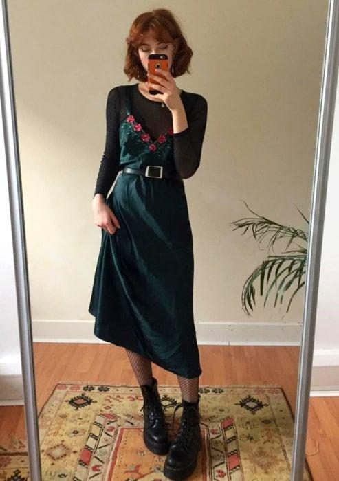 Looks con vestidos y blusas básicas; mujer tomándose selfie frente al espejo, vestido de satín verde con flores, blusa negra transparente, botas Dr. Martens, cabello rojo con corte de honguito y fleco