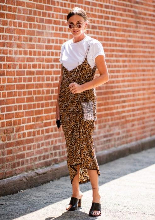 Looks con vestidos y blusas básicas; mujer con vestido oversized de animal print con blusa blanca y lentes pequeños