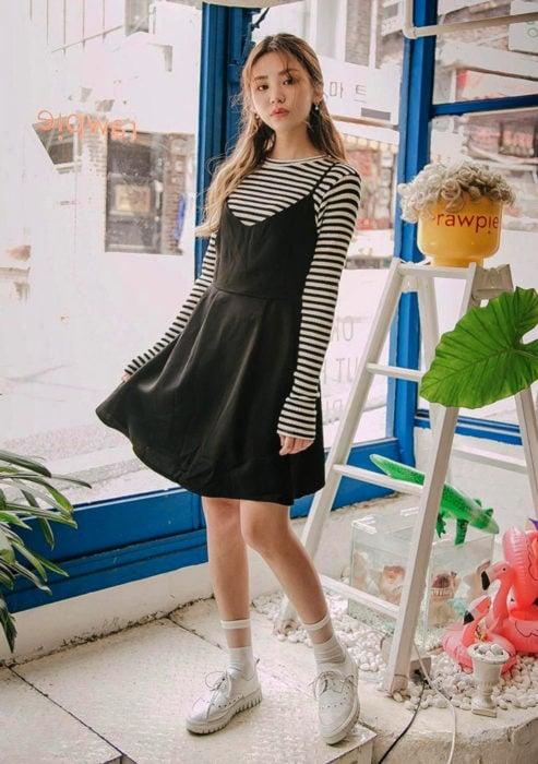 Looks con vestidos y blusas básicas; mujer coreana con vestido sencillo negro, blusa rayada, tenis blancos y peinado de media coleta