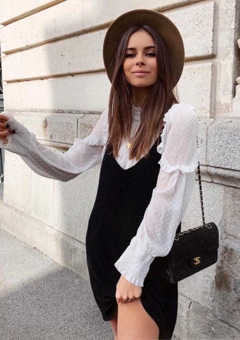 Looks con vestidos y blusas básicas; chica con vestido negro de terciopelo, blusa blanca de holanes y sombrero