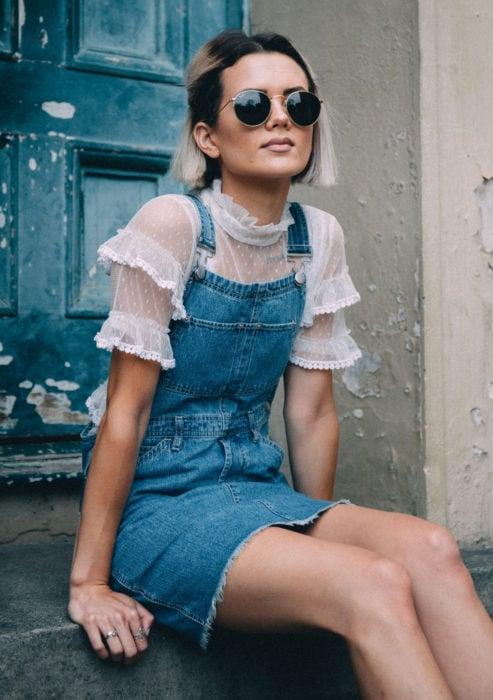 Looks con vestidos y blusas básicas; mujer sentada en escaleras de pórtico, cabello corto color blanco con raíces negras, lentes de sol, vestido overol, blusa de encaje y holanes blancos