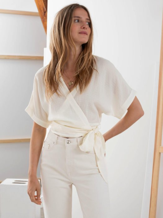 Wrap tops o blusas cache coeur blanca con pantalón blanco a la cintura; mujer con cabello rubio ombré despeinado