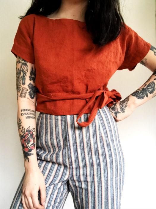 Wrap tops o blusas cache coeur anaranjada; mujer con tatuajes en los brazos