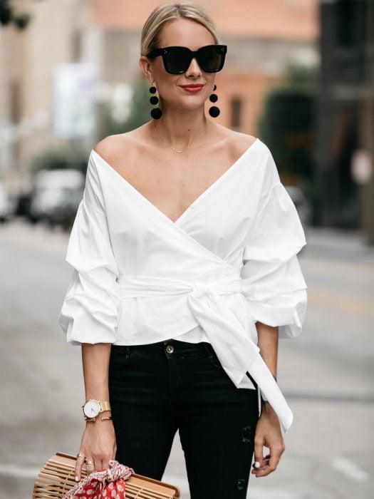Wrap tops o blusas cache coeur blanca sin hombros; mujer rubia con peinado de coleta, lentes cuadrados grandes de sol, aretes negros colgantes y bolsa de madera