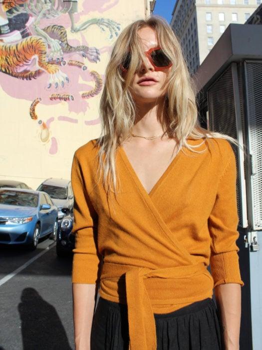 Wrap tops o blusas cache coeur amarillo mostaza; mujer rubia despeinada, con lentes de sol rojos, parada en la calle frente a un mural de tigre
