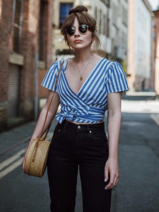 Wrap tops o blusas cache coeur de rayas verticales blancas y azules, jena negro a la cintura, bolsa de mimbre, peinado bun arriba, lentes de sol