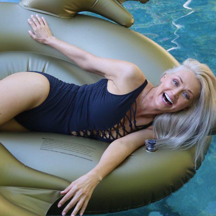 Kathy Jacobs usando traje de baño completo color negro sobre flotador en piscina