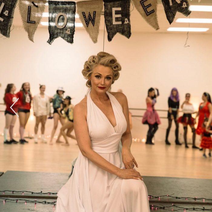 Kathy Jacobs usando vestido blanco tipo halter y cabello recogido