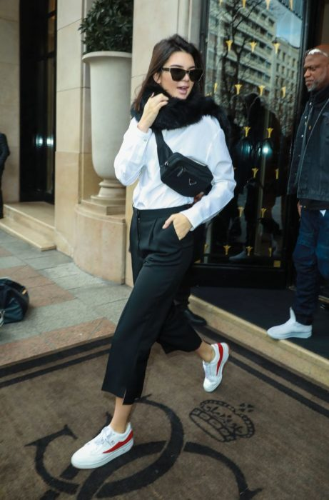 Kendall Jenner usando un outfit de color blanco y negro con una cangurera cruzada en el pecho