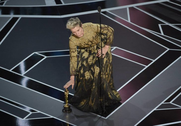 Actriz poniendo su estatuilla de los Óscar en el suelo