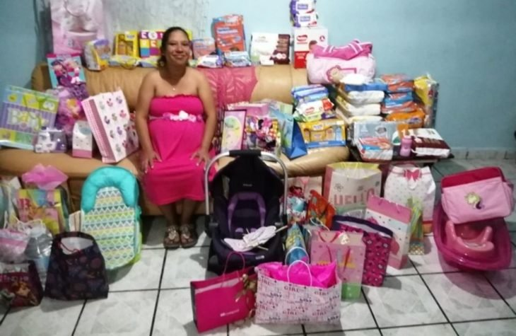 Mujer sentada en un sofá rodeada de regalos para su futura bebé