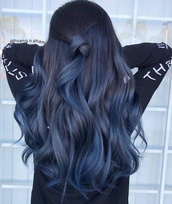 Chica con el cabello teñido de azul mezclilla sujetado en una coleta media y rizos