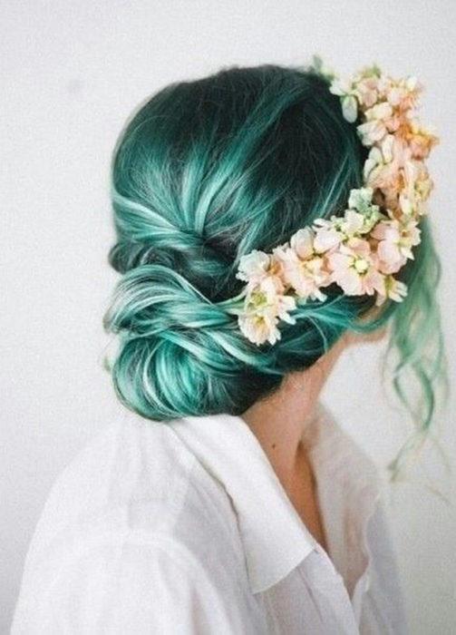 Chica con el cabello verde sujetado en un chongo de color bajo