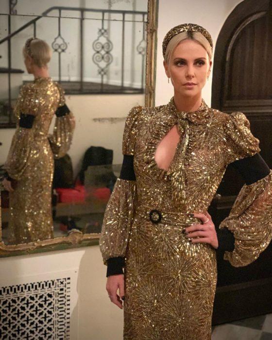Charlize Theron modelando un vestido en dorado