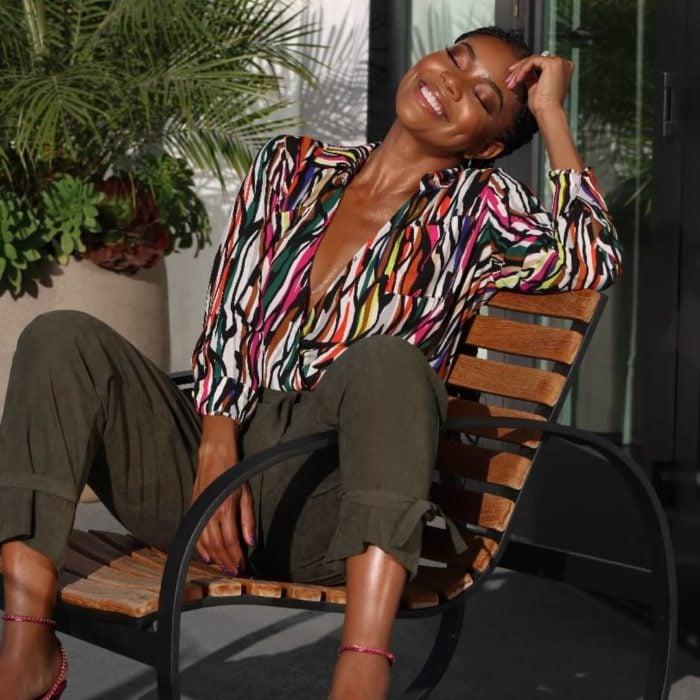 Gabrielle Union sentada en una silla de madera