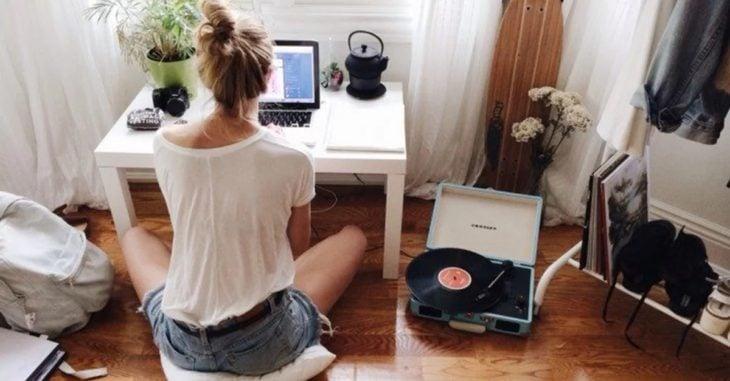 Chica sentada frente al computador escuchando música con un tocadiscos