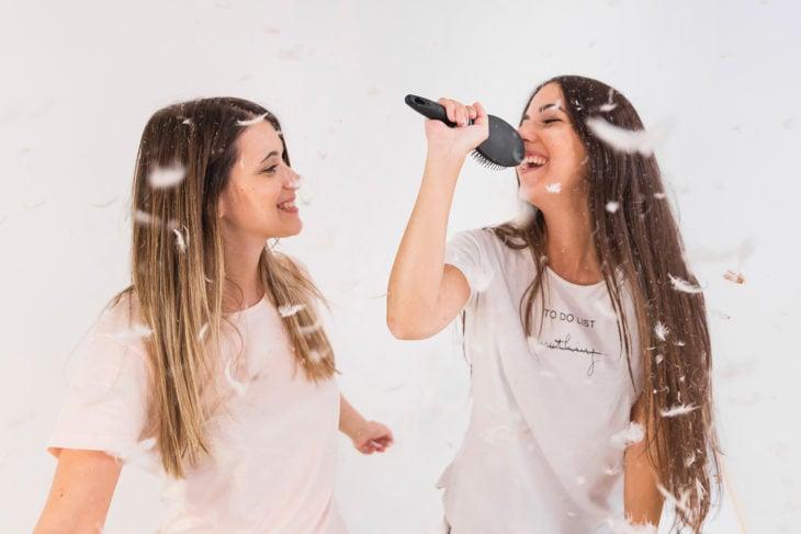 Amigas simulando cantar karaoke con un cepillo para cabello