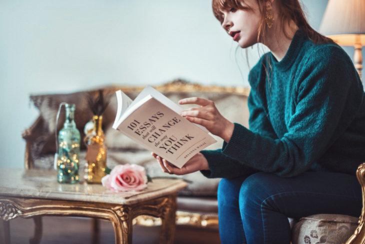 Chica leyendo un libro sentada en un sofá de madera con detalles dorados