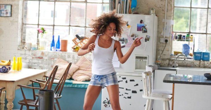 Chicade piel morena bailando en la cocina de un departamento
