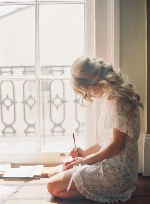 Chica escribiendo una carta a mano sobre una caja de madera