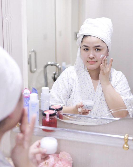 Chica aplicándose crema en el rostro después de haberse bañado