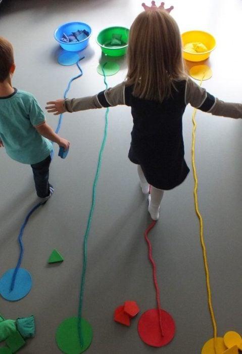 Niños juegan a caminar sin salirse de la linea de color