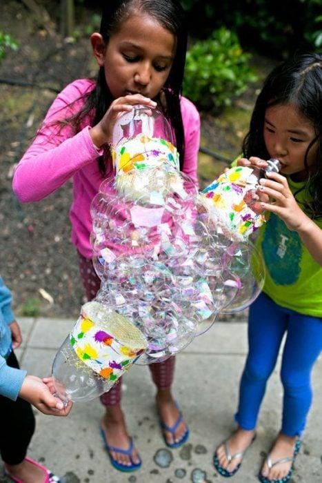Niños hacen burbujas con botellas de plástico