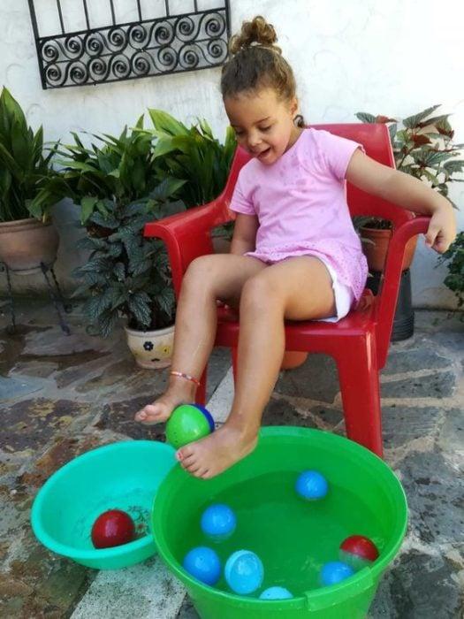 Niña juega a sacar pelotitas del agua con sus pies